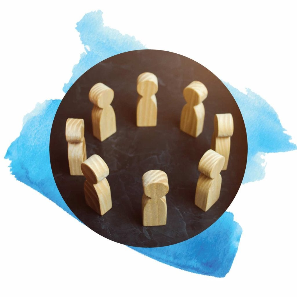 Close shot of a circle of simple wooden people.