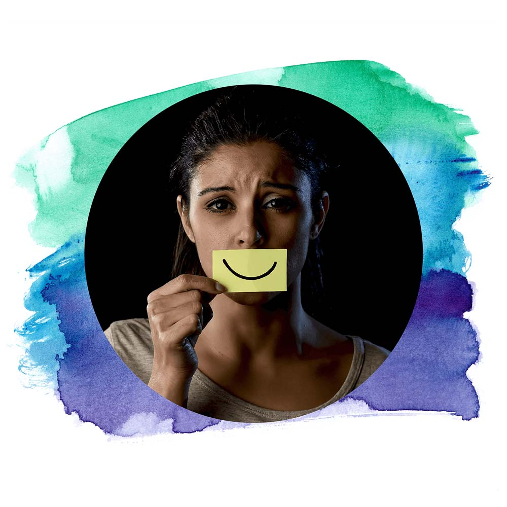 Sad woman holding post-it in front of her mouth with a smile drawn on.